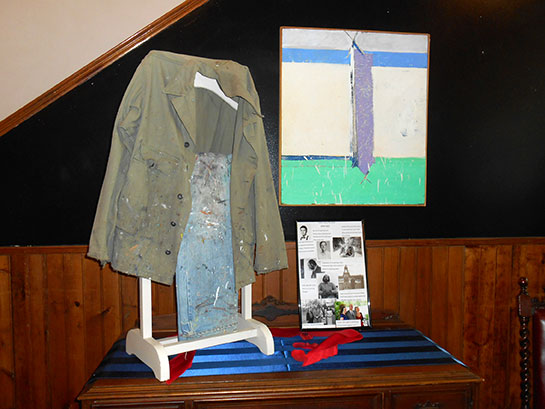 Lewis's paint clothing, his army jacket, and paint pants along with his photos. The small abstract in this photo depicts his earliest of abstracts and his funky framing style. He used house paint since it was cheap to buy. His later abstracts are done in oil on Masonite.